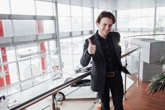 Besuchsauto-vertragshändler Junger Mann auf Autosalonhintergrund Glücklicher Mann zeigt sich Finger Autoverkauf und Mietkonzept Lizenzfreies Stockbild