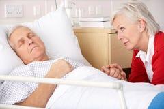 Besuchsehemann der älteren Frau im Krankenhaus Stockbilder