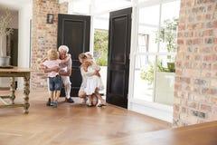 Besuchsgroßeltern verbiegen und knien, um Enkelkinder zu umarmen lizenzfreie stockfotografie