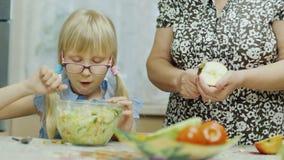 Besuchsgroßmutter Ein Mädchen mit 6-Jährigen isst einen Salat, nahe bei einer älteren Frau säubert einen Apfel mit einem Messer f stock footage
