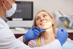 Besuchszahnarzt der reifen Frau an der Klinik lizenzfreie stockfotos