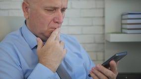 Besvärad affärsman In Office Room som använder mobiltelefonen royaltyfri fotografi