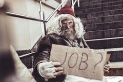 Besvärad almsman som frågar främling om något jobb för honom fotografering för bildbyråer