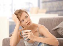 Besvärad kvinna som tänker med tea i hand arkivbild