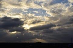Besvärade himlar med sun& x27; s-strålar som igenom bryter Arkivbild