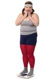 Besviken överviktig kvinna på scale Royaltyfri Fotografi
