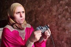 Besviken arabisk egyptisk muslimkvinna som spelar playstation Arkivbild