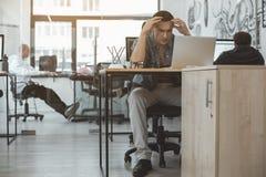 Besviken arbetare som håller ögonen på på bärbara datorn royaltyfri bild