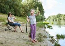 Besviken flickabarnblick på den fångade fisken, grimacing framsida, folk som campar och fiskar, familjaktiv i natur, flod och sko Arkivfoton