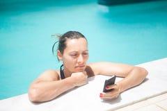 Besviken kvinnaläsningtelefon Arkivfoto