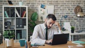 Besviken ledsen person som arbetar med bärbara datorn som uttrycker därefter negativa sinnesrörelser lager videofilmer