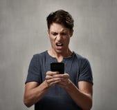 Besviken man med mobiltelefonen royaltyfri bild