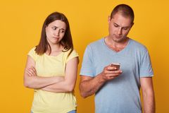 Besviken ung flicka som är trött av att vara bara och att se hennes pojkvän som fokuseras på hans apparat som står med vikta arma arkivfoto