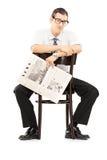 Besviket businesspersonsammanträde på en stol med tidningen arkivfoto