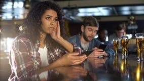 Besviket folk som övervakar online-vad i telefoner, förlorande pengar, i att spela fotografering för bildbyråer