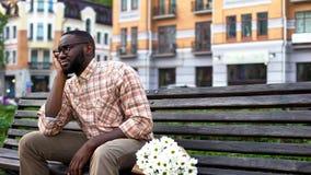 Besviket manligt sammanträde som är ensamt på stadsbänk med blommabuketten som missas datum arkivfoton