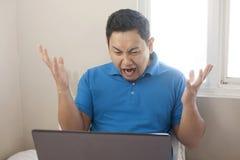 Besviket uttryck för ilsken man som ser bärbara datorn arkivfoto