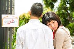 Besvikna asiatiska par framme av ett hus Arkivbilder