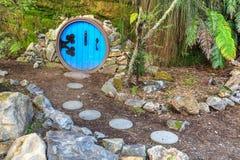 Besynnerligt landskap för trädgård En bana som lite leder till den runda dörren royaltyfri fotografi