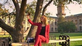 Betäubende junge Studentin, die im Hochschulquadrat sitzt und die selfies, Natur an einem sonnigen warmen Tag empfinden nimmt stock footage