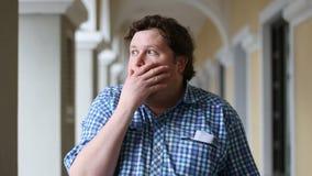 Betäubter fetter junger Mann untersucht mit Erstaunen Kamera und überrascht wird mit positiven Nachrichten stock video footage