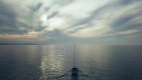 Betäubung flydown 4k Antenne des Segelboots segelnd weg in Sonnenuntergang cloudscape stock video