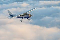 Betäubungsansicht eines blauen und weißen kleinen privaten Cessna-Flugzeuges, das den Himmel über flaumigen Märchenwolken grast lizenzfreies stockfoto