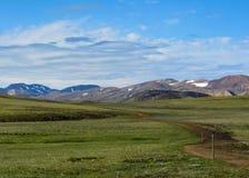 Betäubungsansicht grünen Hvanngil-Bereichs und der bunten Tindafjoll-Rhyolithberge mit Schnee auf dem Hintergrund am sonnigen Tag stockbild