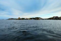 Betäubungsmeer und -himmel mit Wolken, Küstenhäuser stockfoto