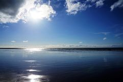 Betäubungsreflexion des Sonnenlichts am Strand in Normandie lizenzfreies stockbild