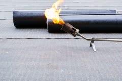 Betún de calefacción y de fusión - la techumbre sentía la instalación del tejado plano fotografía de archivo libre de regalías