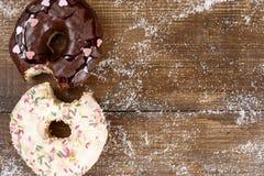 Bet donuts på en trätabell royaltyfri foto