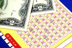 Bet a few dollars on the lottery ticket. Isolated on blue royalty free stock photos