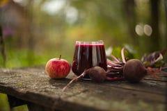 Beta-Apple fruktsaft i exponeringsglas på tabellen Royaltyfri Foto