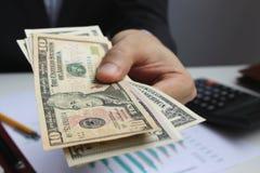 Betaal de Amerikaanse dollar, de dollargeld van het Handgebruik binnen op het bureau royalty-vrije stock foto's