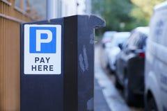 Betaal hier de machine van het autoparkeren op straat en rij van voertuigen buiten huizen stock foto