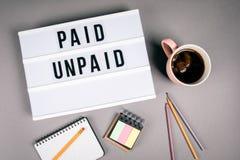 Betaald en Onbetaald Tekst in licht vakje stock fotografie