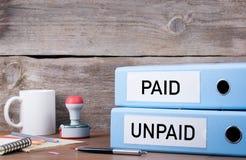 Betaald en Onbetaald Twee bindmiddelen op bureau in het bureau Commerciële bac stock fotografie