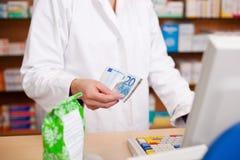 Betala för medicin genom att använda kassa på apotek royaltyfri bild