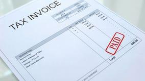 Betald skyddsremsa som stämplas på skattfaktura, kommersiellt dokument, nationalekonomi och affär arkivfoto