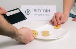 Betaling voor de aankoop van een crypto munt: De koper zet metaalmuntstukken bitcoin in de contant geldschotel De verkoper verzam stock fotografie