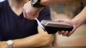Betaling voor diner met kaart en terminal op houten lijstachtergrond in de restaurants stock videobeelden
