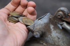 Betaling voor het gas, brandstof, benzine, diesel concept Hand het dalen geld, muntstuk in het blik brandstof royalty-vrije stock foto's