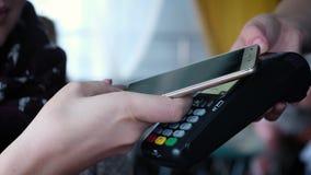 Betaling zonder contact met uw smartphone Het betalen met een smartphoneapparaat op een creditcardterminal Draadloze betaling stock video