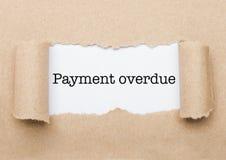 Betalings Achterstallige tekst die achter pakpapier verschijnen royalty-vrije stock fotografie