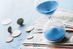 Betalning-, bankrörelse- och skuldbegrepp Olikt pengar och timglas på trätabellen royaltyfri bild