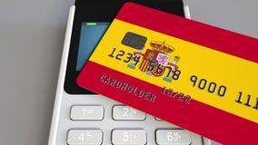 Betalning eller pos.-terminal med kreditkorten som presenterar flaggan av Spanien Spanjoren sälja i minut den begreppsmässiga kom Fotografering för Bildbyråer