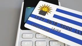 Betalning eller pos.-terminal med kreditkorten som presenterar flaggan av Uruguay Uruguayansk återförsäljnings- kommers eller ban Arkivfoto