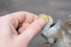 Betalning för gasen, bränsle, bensin, diesel- begrepp Handen som tappar pengar, mynt i kan av bränsle arkivbild