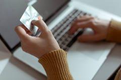 Betalning för kvinnashoppingdanande på datoren genom att använda kreditkorten Arkivbilder